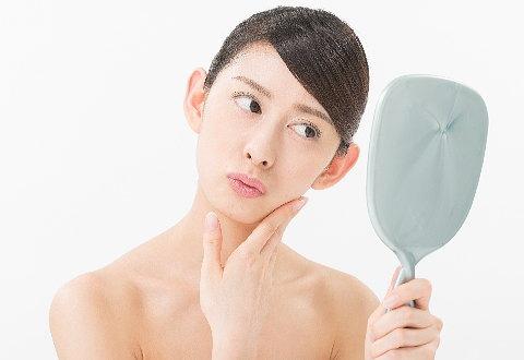 顎ニキビの状態をチェックする女性