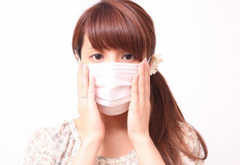 繰り返す顎ニキビをマスクで隠している女性