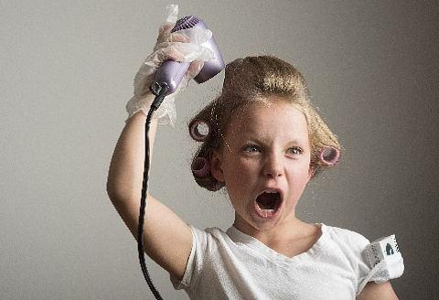 気合を入れて髪をドライヤー乾かす女の子