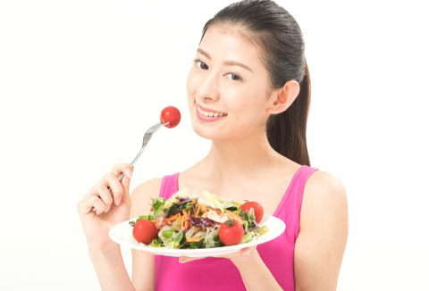 日焼け予防にトマトを食べる女性