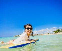夏休みの海で日焼け防止のラッシュがートを着てボディーボードを楽しむ女性