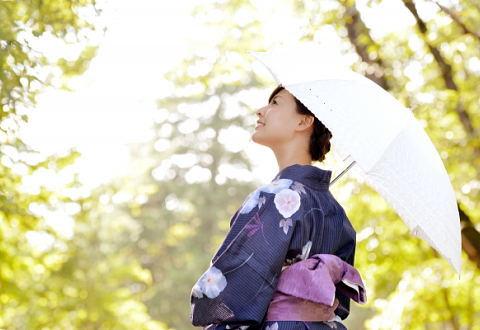 浴衣を着て日傘を持つ30代女性