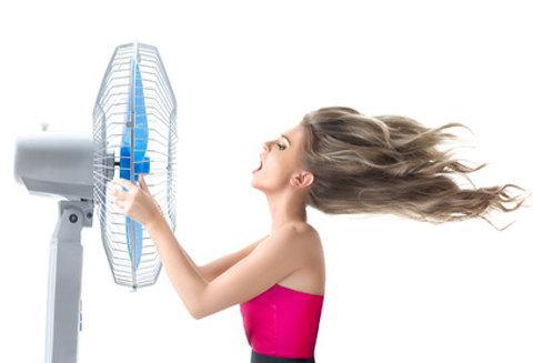 すごい頭の汗を止めるため扇風機で涼む女性