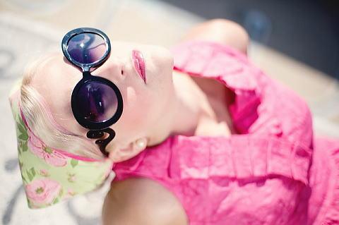 サングラスをかけて太陽を見る女性