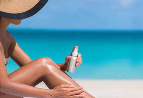 浜辺で日焼け止めスプレーを塗る女性