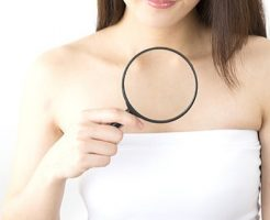 デコルテにできたニキビの状態を虫眼鏡で確認する女性