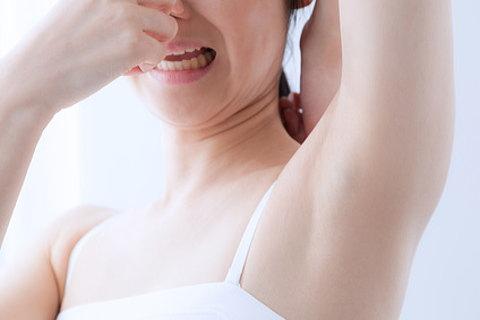 自分の脇の下の臭いに鼻をつまむ女性