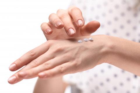 手の甲にハンドクリームを塗る女性